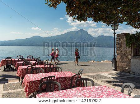 TORRI DEL BENACO - MAY 4, 2016: Garda lake with promenade and restaurant in Torri del Benaco Italy