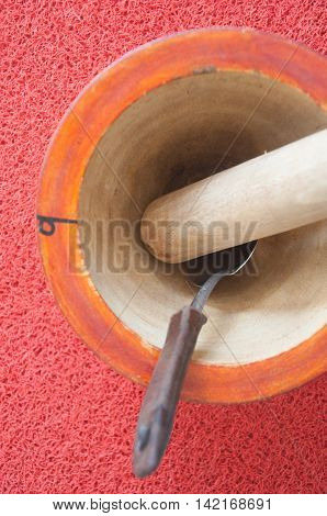 wooden mortar and pestle on red background
