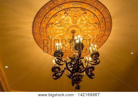 Ornate Chandelier on Old Ceiling in Theater