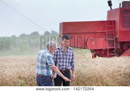 Farmers On Field With Combine Harbester