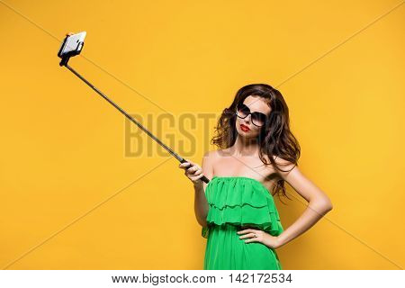 Portrait of young model in green dress and sunglasses posing while making selfie against yellow background. Retouched photo.