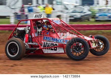 BREDON HILL, UK - MAY 4: An unnamed driver competing in the UKAC autograss series accelerates into the top corner of the oval circuit in his class 10 vehicle on May 4, 2013 in Bredon Hill.