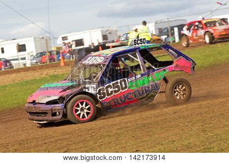 BREDON HILL, UK - MAY 4: An unnamed driver competing in the UKAC autograss series accelerates through the bottom corner on the oval circuit in first position on May 4, 2013 in Bredon Hill.