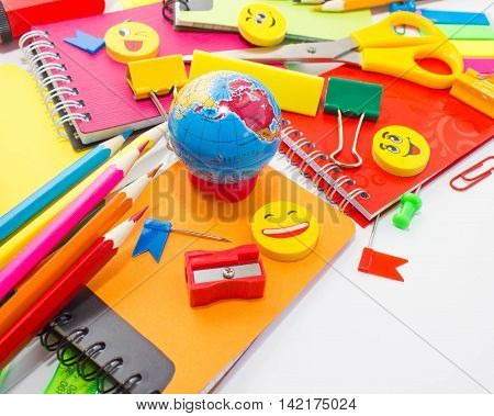 Pens, pencils, erasers, with smileys and a set of notebooks. Schoolchild and student studies accessories. Back to school concept.