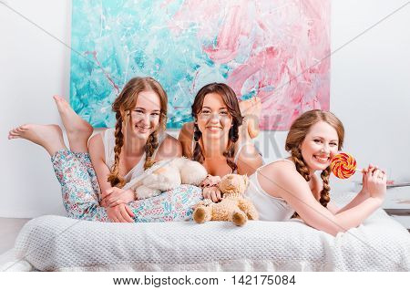 Three Cute Young Girls Sedyat On The Bed In The Room, Are Holdin