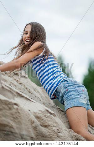 Girl Climbing On The Sand