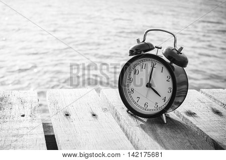 Alarm clock on wood and blurry sea in background. 4 pm. black and white.