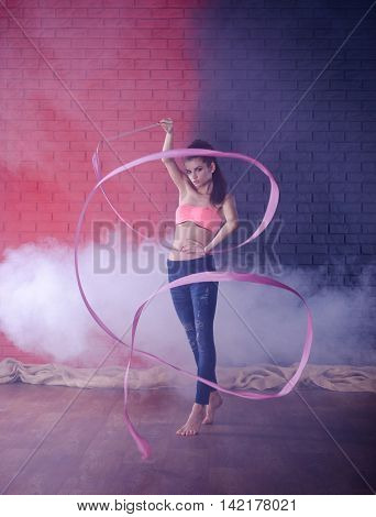 Rhythmic gymnastics. Cute girl dancing with ribbon. Photo in front of brick wall.