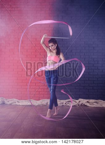 Rhythmic gymnastics. Cute girl dancing with ribbon. Photo in front of brick wall.