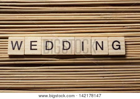 WEDDING word written on wood block at wooden background.