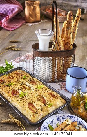Traditional focaccia with tomatoes and bread sticks rustic setting on a wooden table.