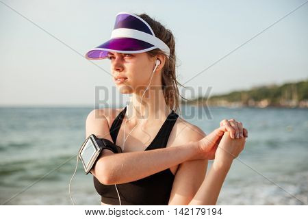 Female young fitness runner doing warm-up routine on beach before running