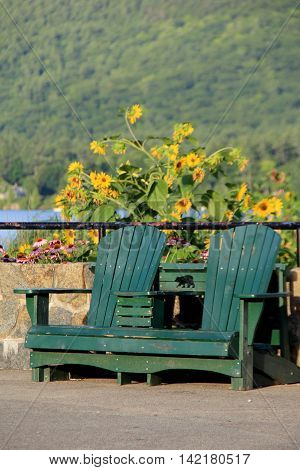 Two Adirondack chairs set side by side on cement, with beautiful flowers  and body of water behind them.