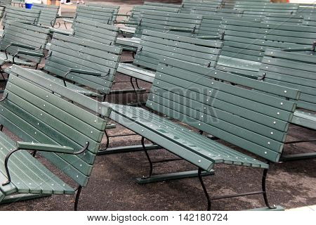 Rows of green benches at an outside sport venue.
