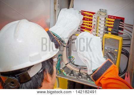 ElectricianElectrician using the digital multimeter to check the resistance and voltage of electric systems in oil and gas industrail.