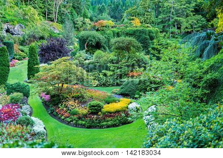 Lush ornate Canadian gardens featuruing well-manicured flower beds bushes and trees