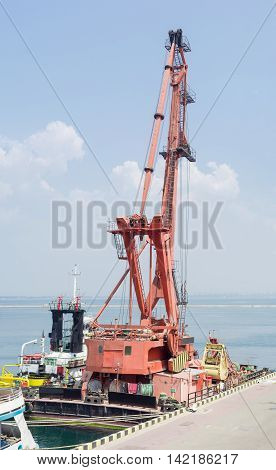Floating crane mounted on pontoon and moored to the berth of the seaport