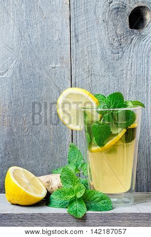 Homemade lacto-fermented refreshing drink with lemon slices ginger and sprigs of mint and lemon balm.