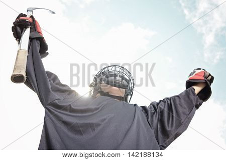 A Portrait of hockey ball player hand up with hockey stick