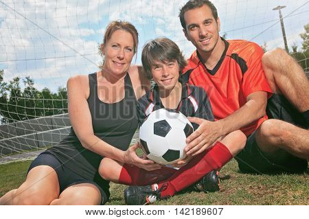 A soccer family portrait sitting on the ground with the ball.