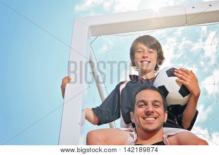 A soccer boy with is father on the shoulder.
