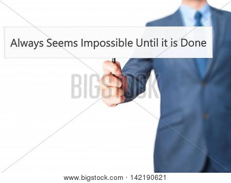 Always Seems Impossible Until It Is Done - Businessman Hand Holding Sign