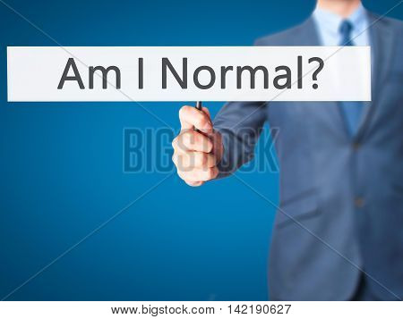 Am I Normal ? - Businessman Hand Holding Sign