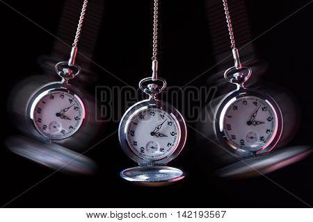 Pocket watch swinging on a chain to hypnotise black background