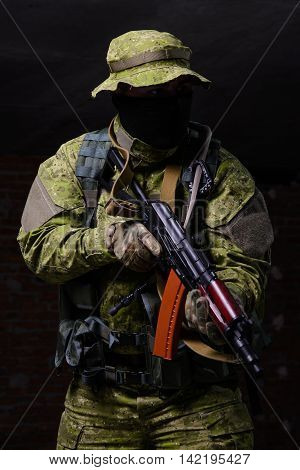 Special forces soldier with assault rifle on dark background
