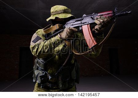 Special forces soldier aiming from rifle on dark background