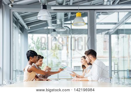 Group of young businesspeople talking and working together in conference room
