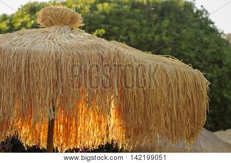 Straw sunshade at sunset times in garden Italy
