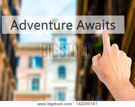 Adventure Awaits - Hand Pressing A Button On Blurred Background Concept On Visual Screen.