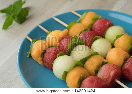 Fruit skewers made of watermelon cantaloupe galia melon and mint leaves. Lined up on a blue plate and fresh mint leaves in the background.