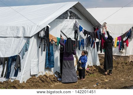 IDOMENI, GREECE - MARCH 17, 2016: Two women try to dry their clothes after heavy rain on March 17 2015 in the refugee camp of Idomeni Greece. For several weeks more than 10.000 refugees and immigrants wait here for the borders to open.