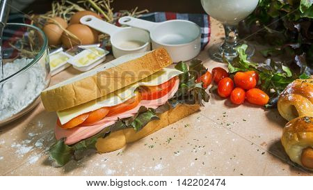big sandwich with ham cheese and vegetables on woodboard