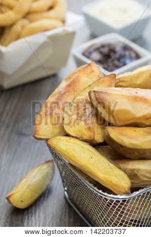 Oil free baked potato wedges in a mini wire basket on a wooden table with onion rings barbeque sauce and mayonnaise in the background.