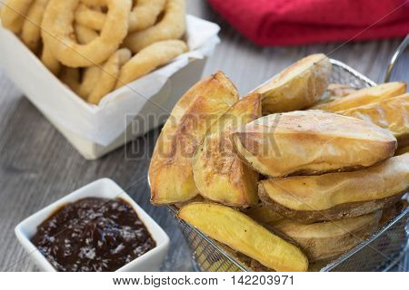 Oil free baked potato wedges in a mini wire basket with baked onion rings and barbeque sauce on a wooden table and red cloth in the background.