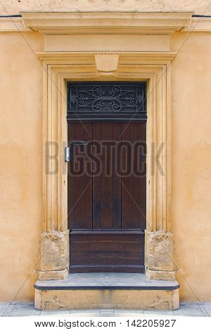 Old closed decayed wooden door on yellow wall facade