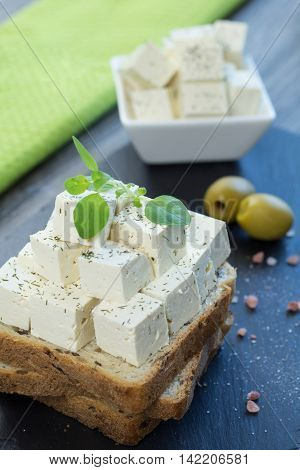 Tofu feta cheese with fresh oregano on a whole grain toast with linseed along with himalayan salt and two green olives on a black stone tray.