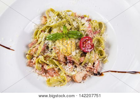 pasta with octopus,tomatoes,yolk and basil isolated on white background