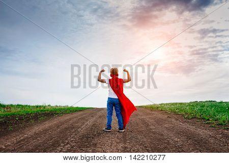 the little preschool boy plays the superhero outdoors