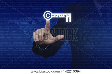 Businessman pressing copyright key icon over digital world map and binary code Copyright and patents concept Elements of this image furnished by NASA