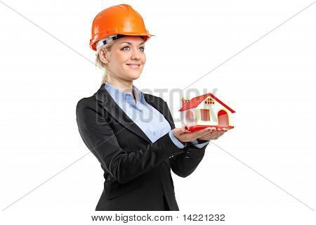 A Smiling Forewoman Wearing Helmet And Holding A Model House