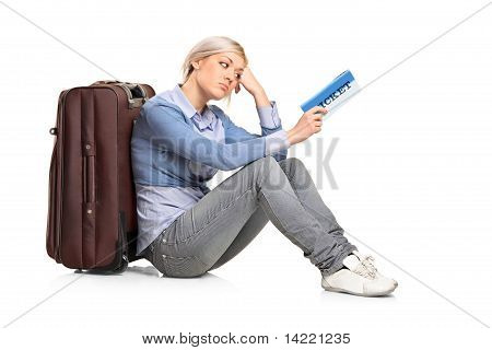 A Tourist Girl Sitting Near A Suitcase With A Ticket In Her Hand