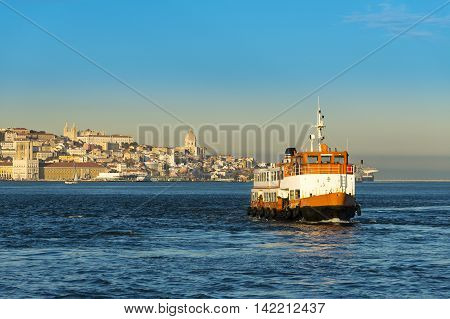 Passenger boat (Cacilheiro) crossing the Tagus River with the Lisbon skyline as background; Concept for travel in Lisbon Portugal