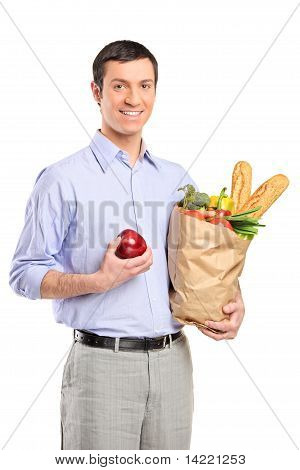 Smiling Man Holding An Apple, A Bag Full With Bread And Vegetables