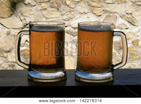 Pints of draft beer on the wooden desk over old stone wall background