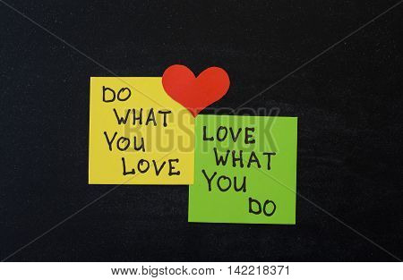 Yellow and green note paper with red heart on black wooden background. 'Love What You Do and Do What You Love' notes pasted on blackboard.
