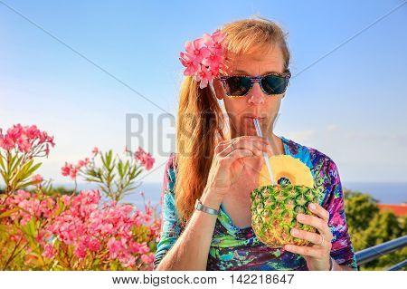 European middle aged woman drinking pine apple juice near pink oleander